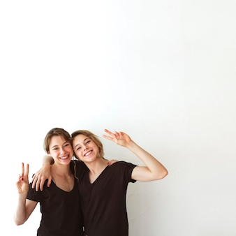 Two sisters making victory sign against white background