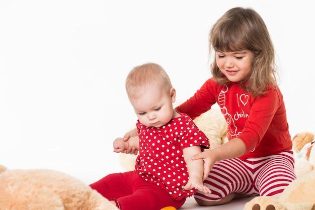 Две сестры играют с плюшевыми игрушками