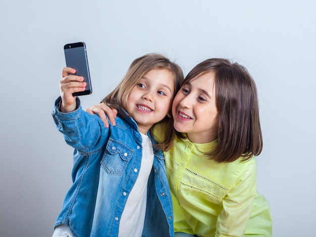 Two sisters posing and taking selfies in the studio.