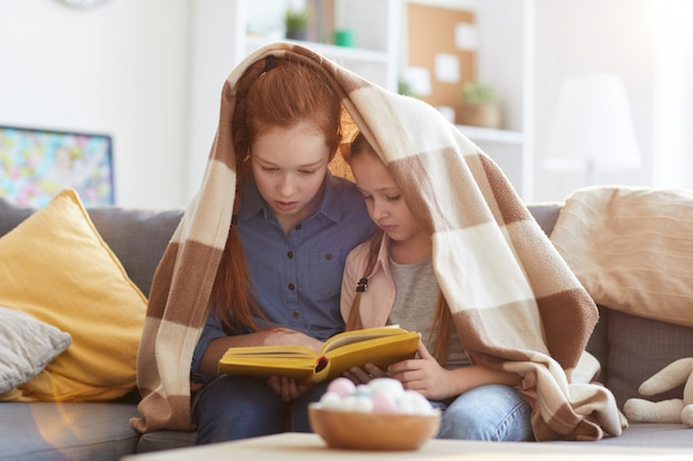 Two sisters reading book
