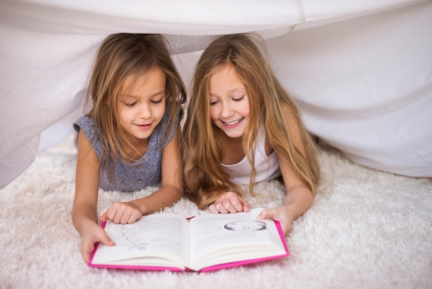 Two sisters reading their favorite book