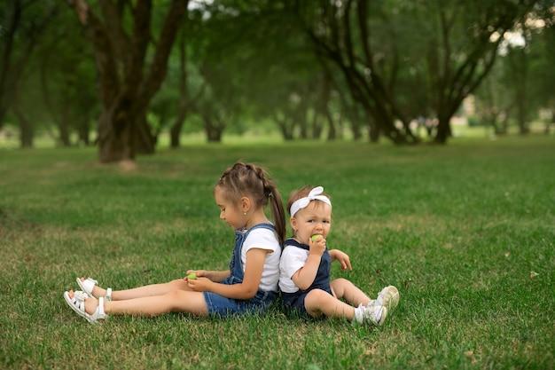 Две сестры сидят в парке на траве и едят яблоки