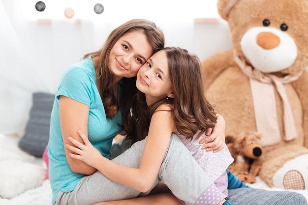 子供部屋に座って抱きしめる2人の姉妹