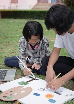 Two sisters sitting on green grass ground floor.painting color on canvas,with happy feeling,good hobby.doing activity together