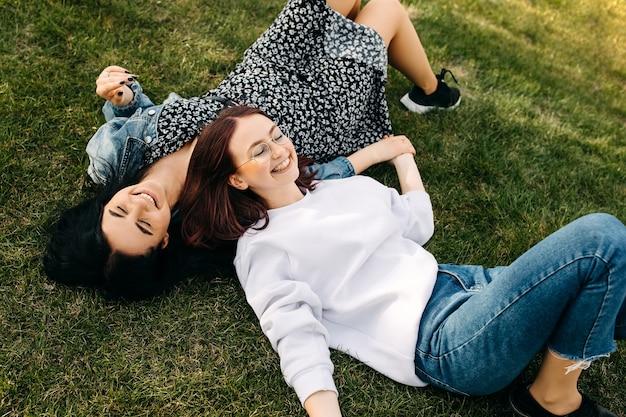 公園の緑の芝生の上に横たわって屋外で時間を過ごす笑顔の 2 人の姉妹