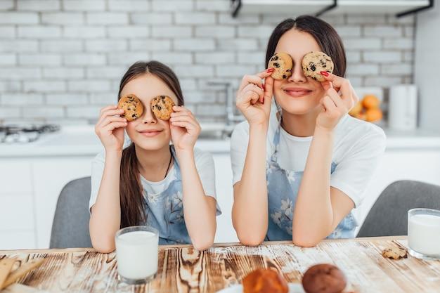 Две сестры, улыбаясь, играют со своими кексами и пьют молоко