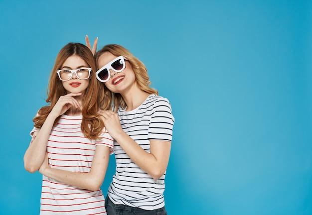 2人の姉妹が並んでファッショナブルな服のスタジオの豪華な友情の青い背景に立っています