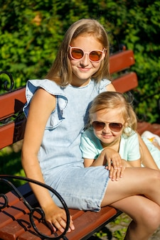 Two sisters in sunglasses sit in the park on a bench