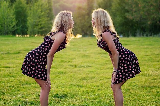 두 자매 쌍둥이 아름다운 곱슬 금발 행복한 젊은 이빨 미소 세련된 드레스를 입고 여름 공원 일몰 광선 필드 배경에서 재미