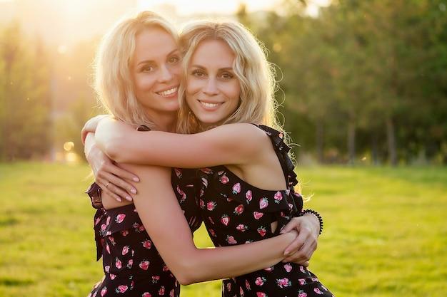 두 자매 쌍둥이 아름다운 곱슬 금발 행복한 젊은 이빨 미소 여성 여름 공원 일몰 광선 필드 배경에서 껴안고 세련된 드레스