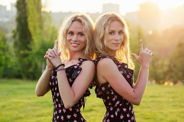 두 자매 쌍둥이 아름다운 곱슬 금발 행복한 젊은 이빨 미소 여성 여름 공원 일몰 광선 필드 배경에서 포즈를 취하는 세련된 드레스