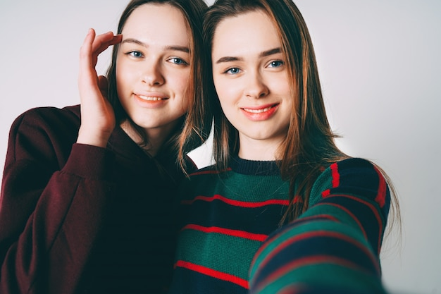 Two sisters twins beautiful girls in casual taking selfie