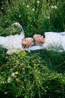 Two sisters twins lying on green grass