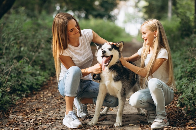 Two sisters with their dog in park