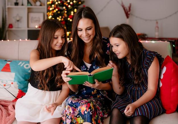 Due sorelle e una giovane madre a casa a tempo di natale seduto sul divano nel soggiorno sorridente madre lettura libro alle figlie figlia più giovane sorridente indicando il libro