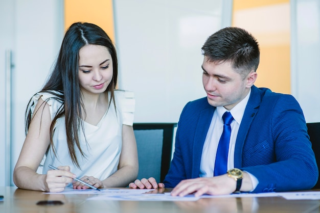 Two sitting business people looking at documents