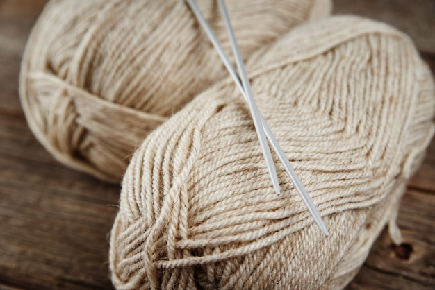 Two skeins of woolen yarn and needles for knitting on a wooden surface