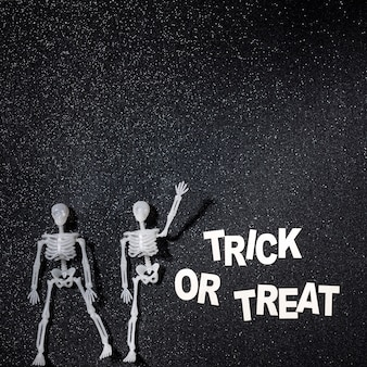 Two skeletons in a trick or treat composition