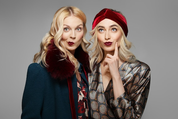 Two skeptical fashion models in retro dress and coat. clean fresh face of pretty girl with natural makeup.