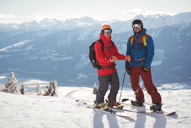 雪に覆われた山に一緒に立っている2人のスキーヤー
