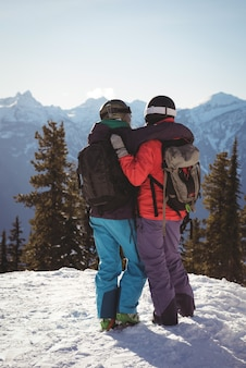 Two skiers standing together with arm around on snow covered mountain
