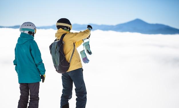 ヨーロッパのスキーリゾートで最も高い山を越えて写真を撮る2人のスキーヤー