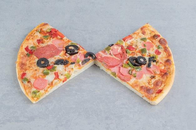 Due fette di pizza esposte su marmo