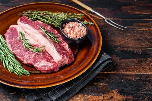 얇게 썬 생 스트립로인 스테이크 2개 또는 뉴욕 스테이크, 쇠고기 고기. 어두운 나무 배경입니다. 평면도. 공간을 복사합니다.
