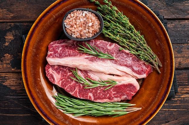얇게 썬 생 스트립로인 스테이크 2개 또는 뉴욕 스테이크, 쇠고기 고기. 어두운 나무 배경입니다. 평면도.