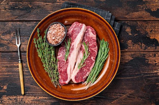 Два нарезанных стейка raw striploin или стейки new york, говядина. темный деревянный фон. вид сверху.