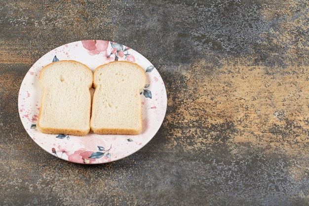 Two slices of bread on colorful plate.