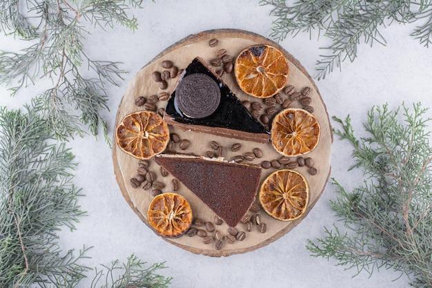 Due fette di torta con fette d'arancia e chicchi di caffè su un pezzo di legno. foto di alta qualità
