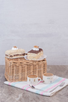 Two slices of cakes and coffees on tablecloth.