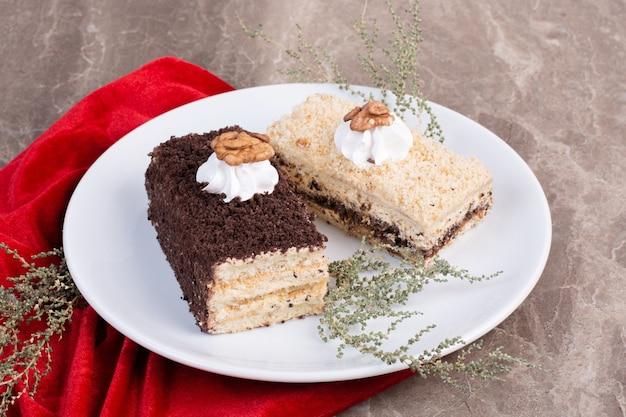 Due fette di torte sul piatto bianco con tovaglia rossa.