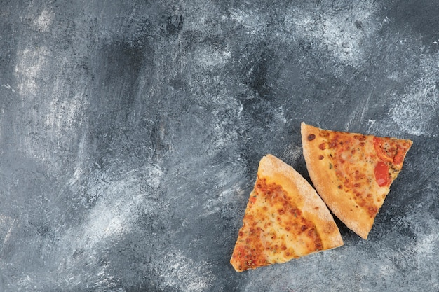 Two slices of delicious fresh pizza on stone background.