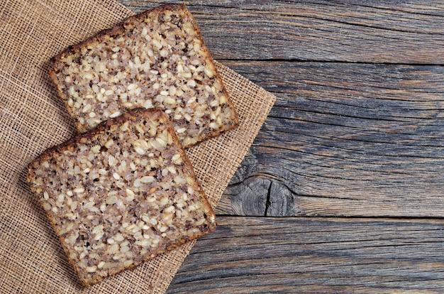 古い木製のテーブルに異なる種のパンの2つのスライス、コピースペースの上面図