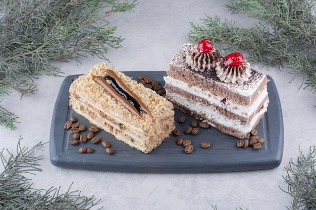 コーヒー豆と暗いプレート上のケーキの2つのスライス。高品質の写真