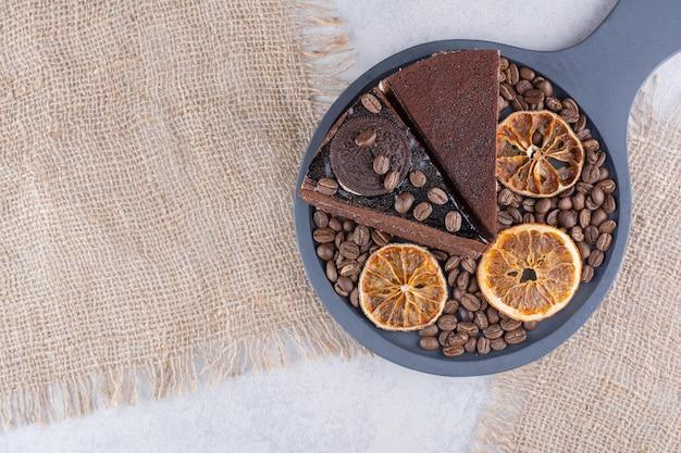 コーヒー豆とオレンジスライスのチョコレートケーキの2つのスライス。高品質の写真