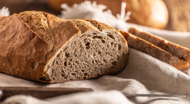 갓 구운 빵 두 조각을 덩어리 위에 놓고 칼로 한 면에 린넨 천을 얹습니다.