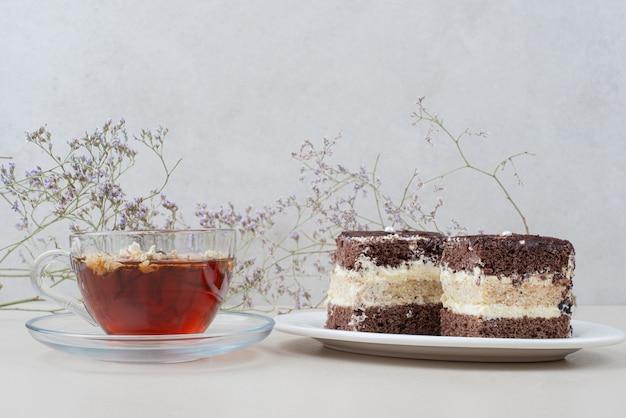 Due fette di torta tiramisù e tazza di tè sulla superficie bianca