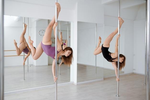 극 춤 훈련에 두 명의 슬림 여성. 체육관에서 운동하는 전문 여성 댄서, 장대 댄스