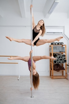 극 춤 운동에 두 명의 슬림 여성. 체육관에서 운동하는 전문 여성 댄서, 장대 댄스