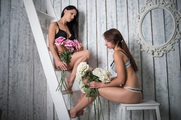나무 벽 배경 위에 앉아 섹시 속옷에 두 슬림 젊은 여성