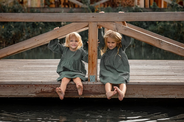 Two small beautiful children girls on a wooden pier on the lake shore