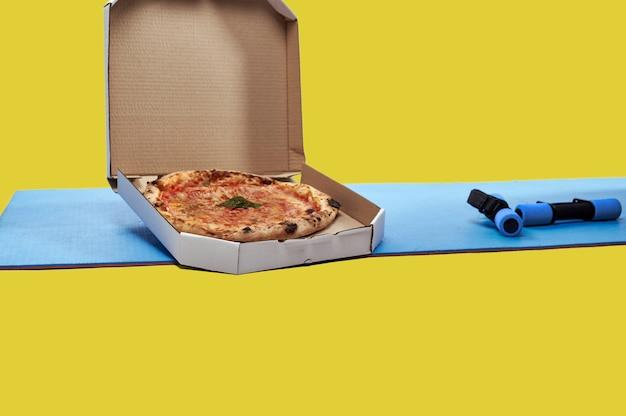 2つの小さな青いダンベルと青いフィットネスまたはヨガマットの上においしいピザが入った箱。孤立。ダイエット、不健康な食べ物、トレーニングツールの概念