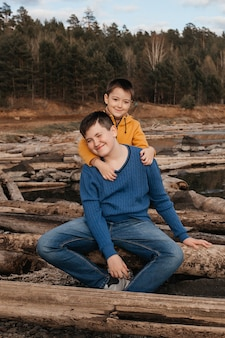 2人の小さな男の子が川のほとりの抱擁に座っています。友情と兄弟愛の概念。野外レクリエーション。