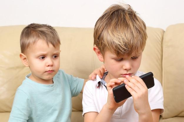 Два маленьких мальчика смотрят на мобильный телефон