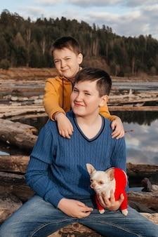 2人の小さな男の子がチワワ犬の腕の中で川のそばの丸太に抱擁に座っています。友情と兄弟愛の概念。野外レクリエーション。
