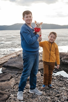 Two small boys stand by the river in the arms of a chihuahua dog. the concept of friendship and brotherhood. outdoor recreation.