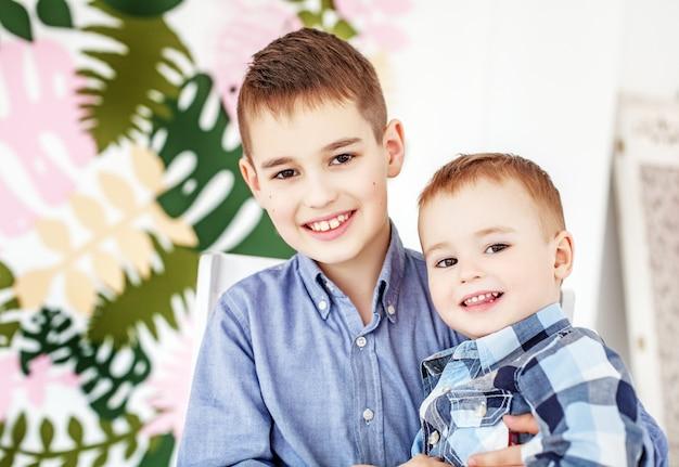 Два маленьких брата обнимаются и смеются.